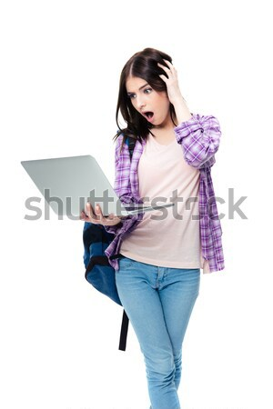 Surprised woman standing and looking on laptop screen Stock photo © deandrobot