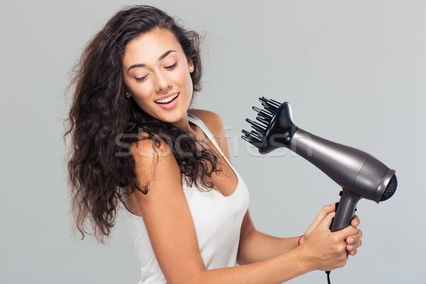 Smiling young woman dries her hai Stock photo © deandrobot