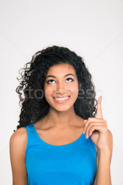 Afro american woman pointing finger up at copyspac Stock photo © deandrobot