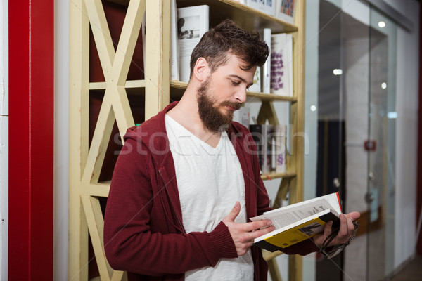 Concentrated guy holding glasses and reading book in library  Stock photo © deandrobot
