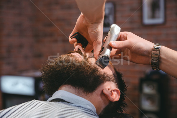Young bearded man during beard grooming in barber shop Stock photo © deandrobot