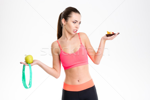 Woman holding apple, mesuring tape and cake making a choice Stock photo © deandrobot