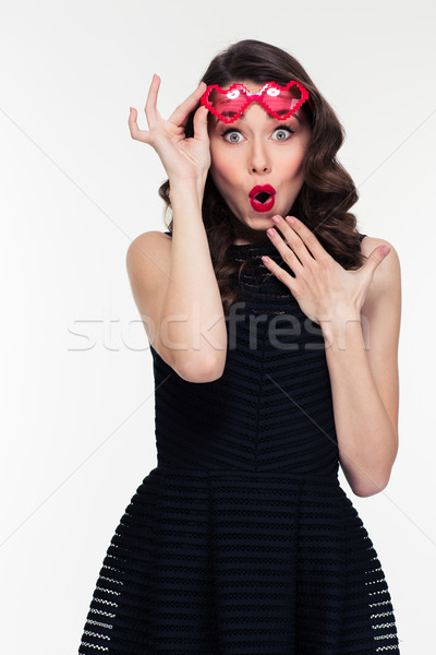 Amusing amazed curly young woman in red heart shaped glasses Stock photo © deandrobot