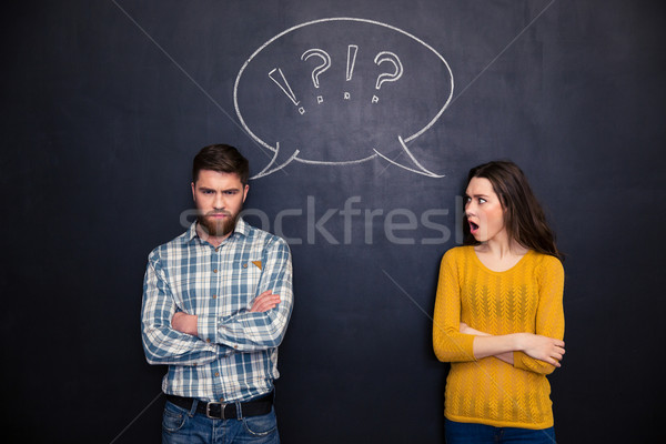 Frowning couple standing after argument over chalkboard background Stock photo © deandrobot