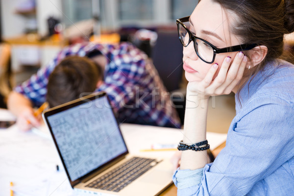Tired woman with laptop sitting in meeting room  Stock photo © deandrobot