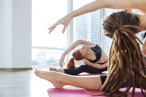 Two woman stretching on the floor in yoga center together Stock photo © deandrobot