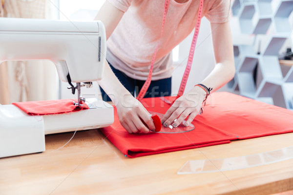 Woman seamstress working making pattern on red fabric Stock photo © deandrobot