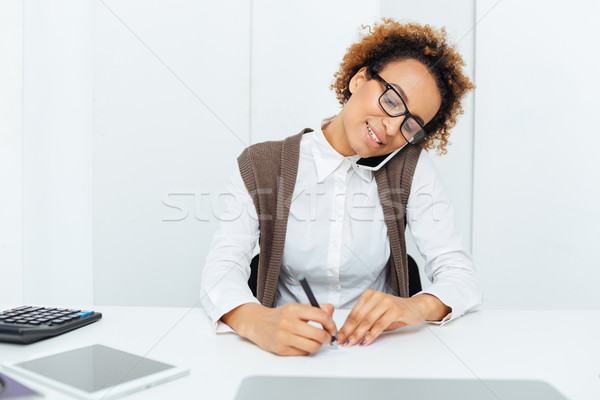 Happy african woman accountant talking on cell phone and writing  Stock photo © deandrobot