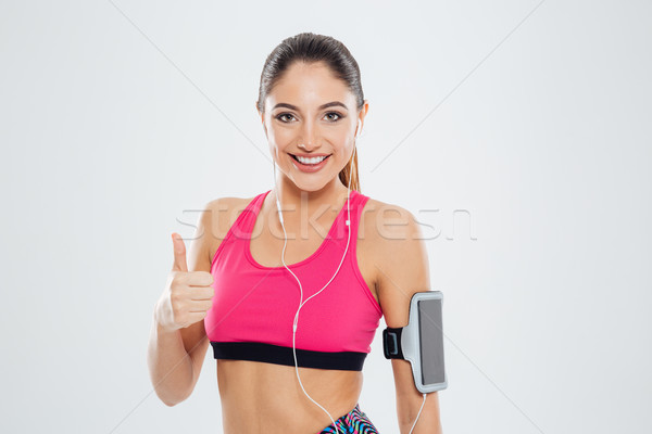 Smiling fitness woman with earphones showing thumb up Stock photo © deandrobot