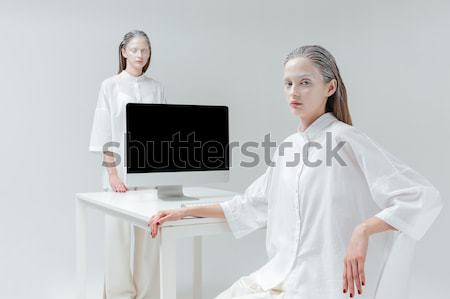 Two woman sitting and standing beside table with computer, pc Stock photo © deandrobot
