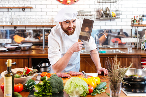 Smiling chef cook with cleaver knife cutting meat and vegetables Stock photo © deandrobot