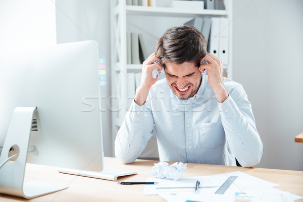 Mad desperated businessman sitting in office Stock photo © deandrobot