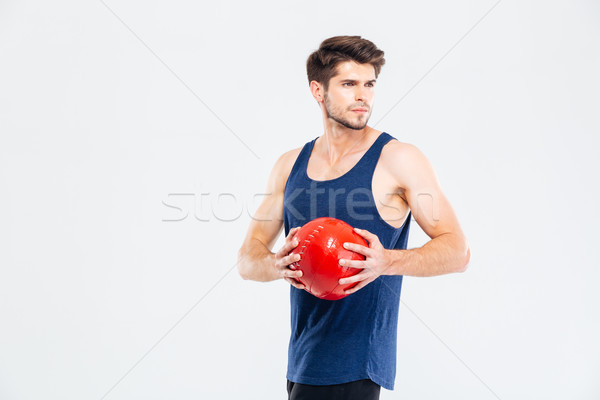 Concentrated young man athlete diong exercises with red ball Stock photo © deandrobot