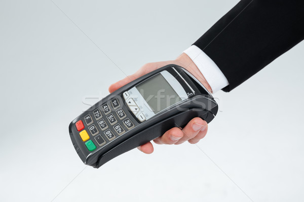 Hand of businessman holding payment terminal Stock photo © deandrobot