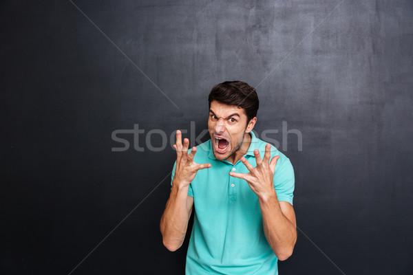 Mad wściekły młody człowiek stałego tablicy Zdjęcia stock © deandrobot