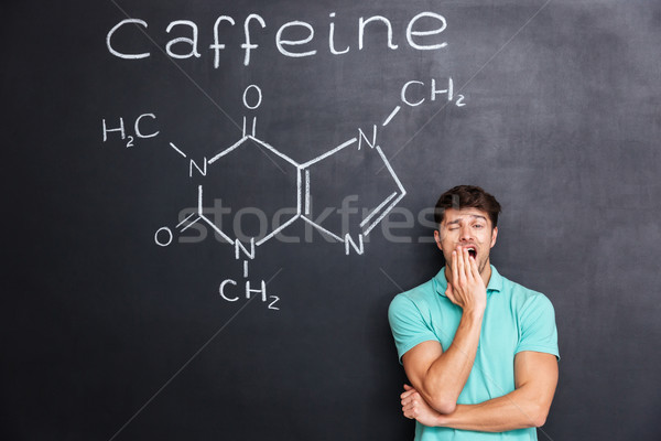 Exhausted fatigued man yawning over chalkboard with drawn caffeine molecule Stock photo © deandrobot