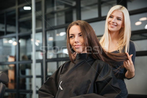 Hairdresser giving a new haircut to female customer at parlor Stock photo © deandrobot