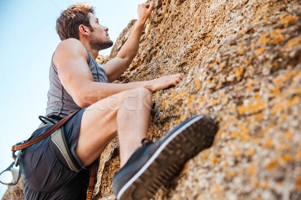 Jovem escalada para cima rocha penhasco Foto stock © deandrobot