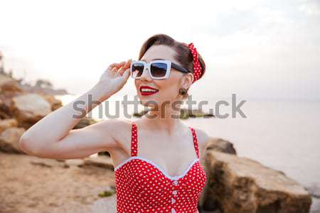 Smiling beautiful pinup girl in headband and suglasses having fun Stock photo © deandrobot