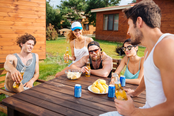 Smiling young people talking and drinking beer outdoors Stock photo © deandrobot