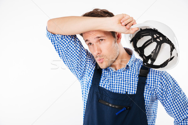 Portrait of tensed young constructor feeling exhausted after work Stock photo © deandrobot