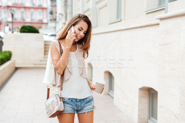 Girl talking on the mobile phone and drinking coffee Stock photo © deandrobot
