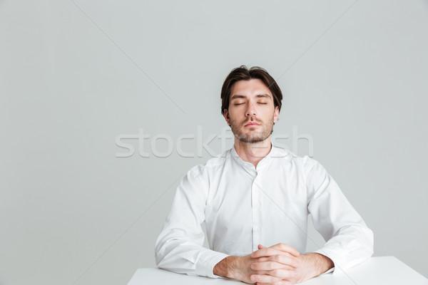 Adam oturma tablo gözleri kapalı Stok fotoğraf © deandrobot