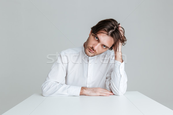 Thoughtful young man in white shirt sitting at the table Stock photo © deandrobot
