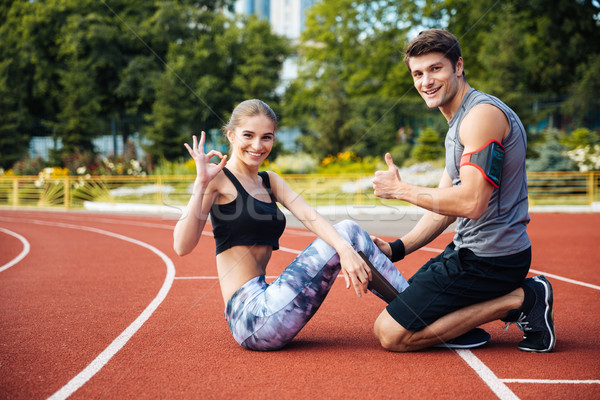 Young beautiful happy couple doing sports exercises at the stadium Stock photo © deandrobot