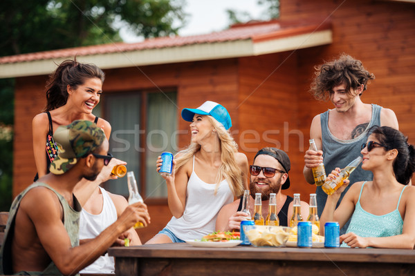 Group of cheerful young people drinking beer and laughing outdoors Stock photo © deandrobot