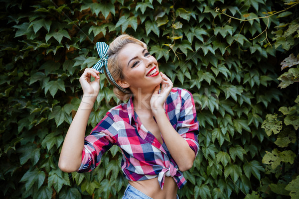 Stock photo: Cheerful lovely pin up girl standing and laughing