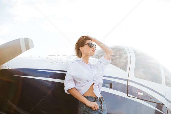 Woman in sunglasses standing outdoors near small private plane Stock photo © deandrobot