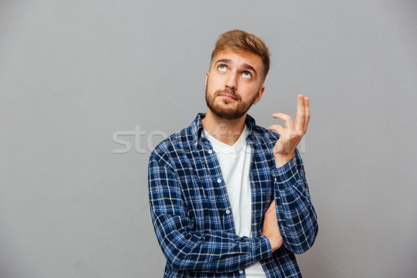Portrait of a casual pensive man standing and looking away Stock photo © deandrobot