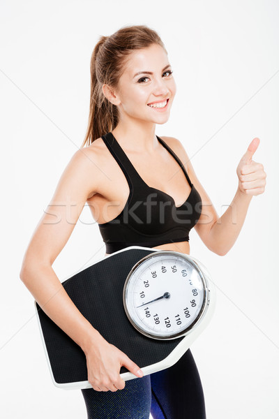 Happy sportswoman holding weight scales and showing thumbs up gesture Stock photo © deandrobot