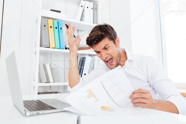 Angry desperate businessman sitting at the table and holding documents Stock photo © deandrobot