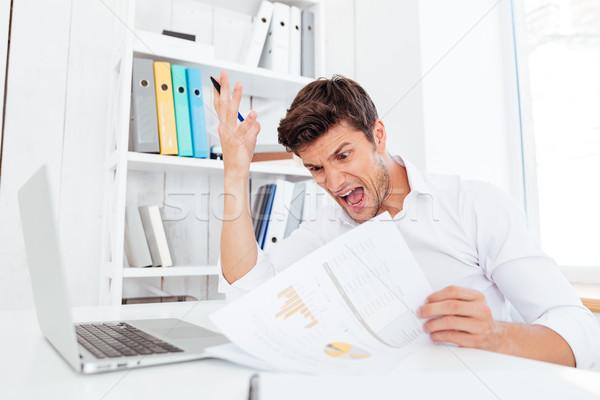 Mérges kétségbeesett üzletember ül asztal tart Stock fotó © deandrobot