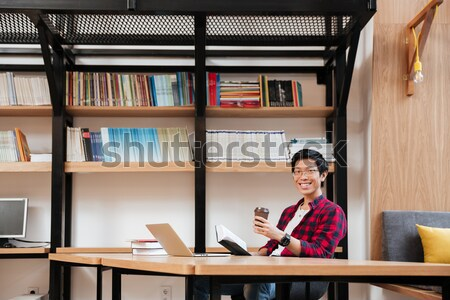 Cheerful asian male using laptop at the library Stock photo © deandrobot