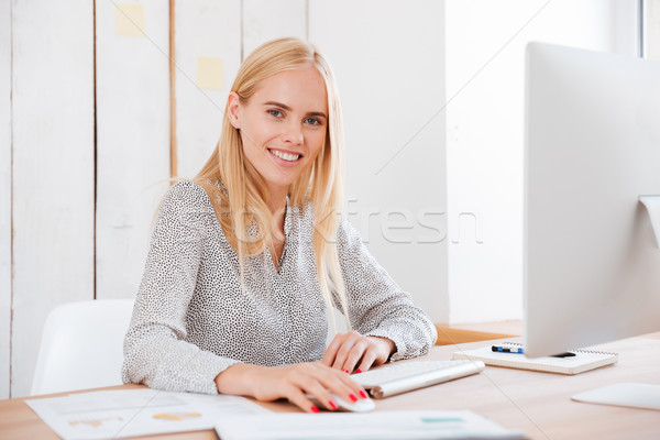 Happy young business woman sitting with computer in office Stock photo © deandrobot