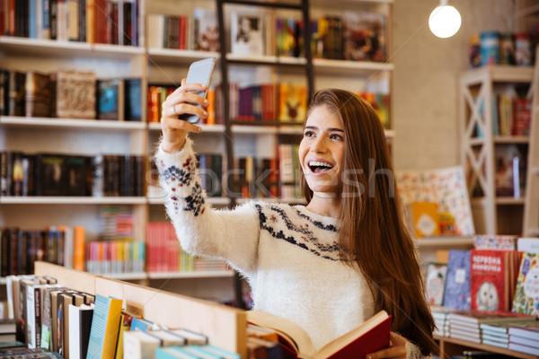 Glimlachend gelukkig meisje vergadering bibliotheek portret Stockfoto © deandrobot