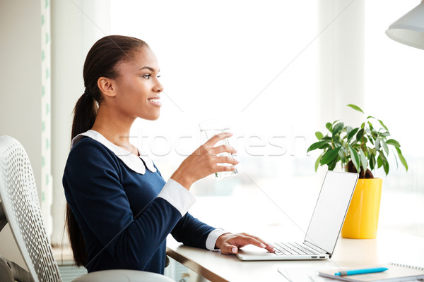 Stock photo: African business woman with water in office
