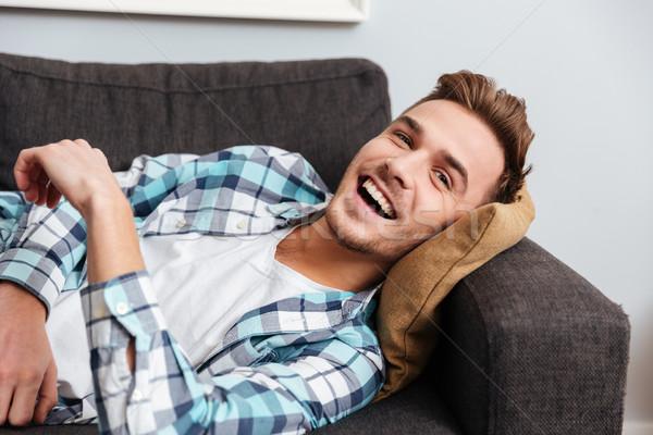 Feliz joven mentiras sofá mirando retrato Foto stock © deandrobot