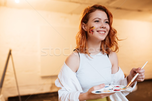 Cheerful young redhead woman painter with oil paints on face Stock photo © deandrobot