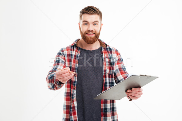 Man in shirt holding clipboard and giving pencil to camera Stock photo © deandrobot