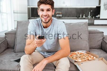 Homme poussant bouton télécommande pizza Photo stock © deandrobot