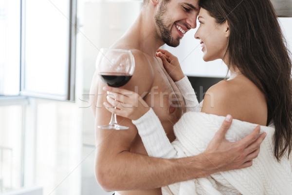 Cheerful couple hugging and drinking red wine at home Stock photo © deandrobot
