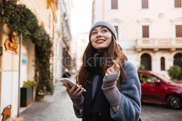 Woman using cell phone and eating ice cream in city Stock photo © deandrobot