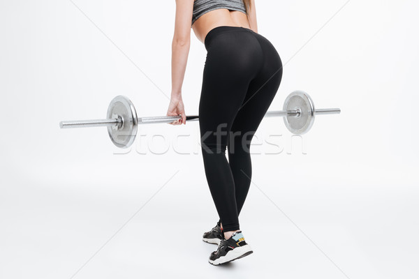 Back view portrait of a fit women body holding barbell Stock photo © deandrobot