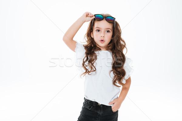 Maravilhado little girl óculos de sol em pé posando Foto stock © deandrobot