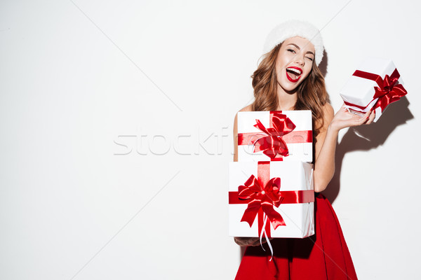 Excited woman in red santa claus outfit holding stack presents Stock photo © deandrobot