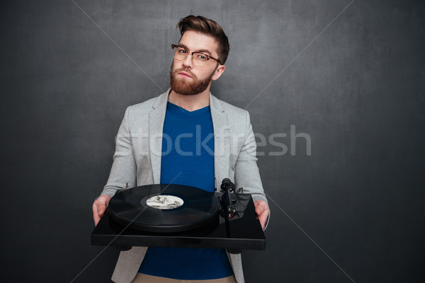 Handsome bearded young man in glasses syanding and holding turntable Stock photo © deandrobot